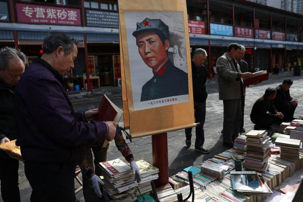 Customers looking at books beside a painting of former Chinese Communist Party leader Mao Zedong displayed in a stall at Panjiayuan Antique market in Beijing on Oct 11, 2017.