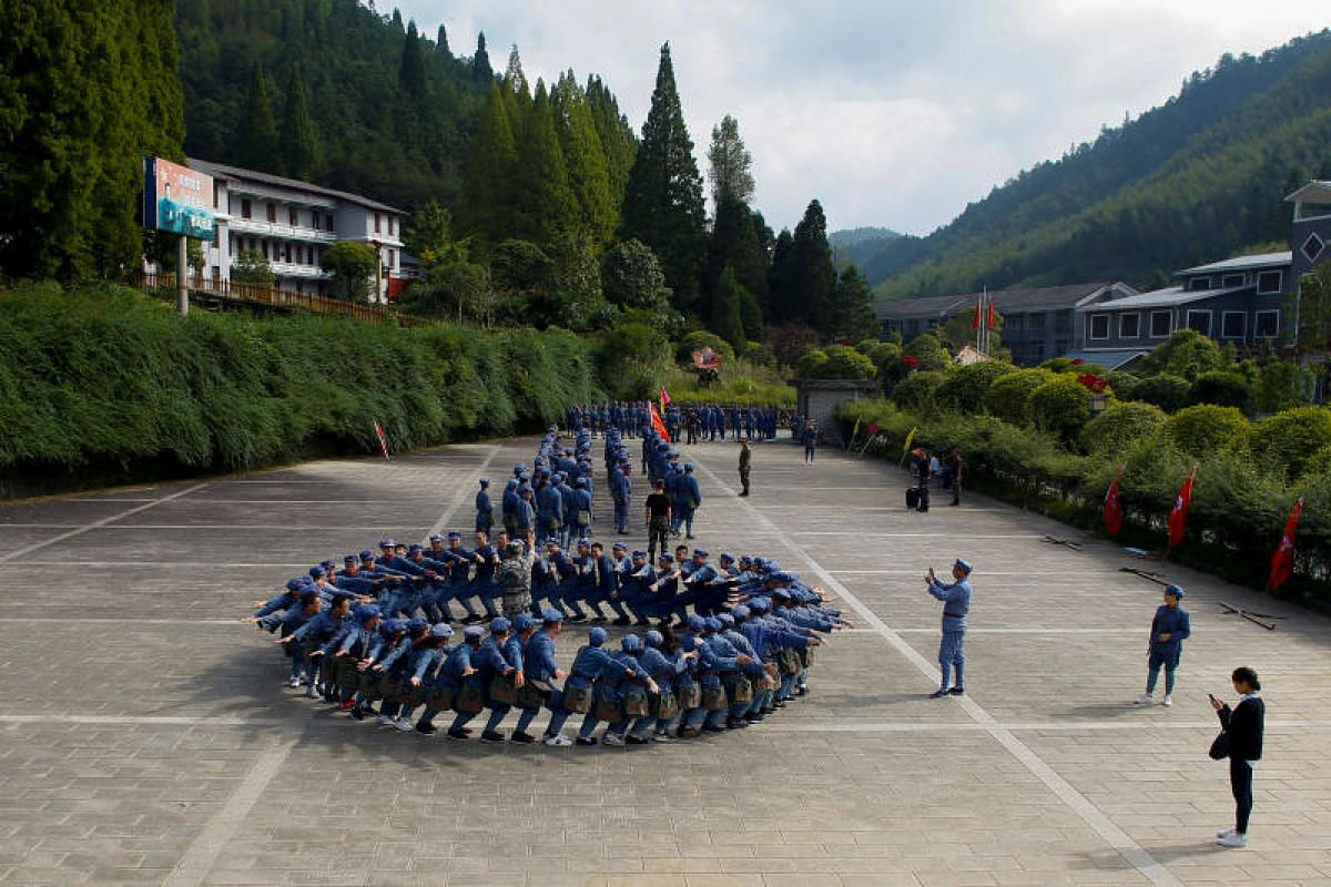 Participants in replica red army uniforms taking part in a Communist team-building course extolling the spirit of the Long March in the mountains outside Jinggangshan, Jiangxi province on Sept 14, 2017.