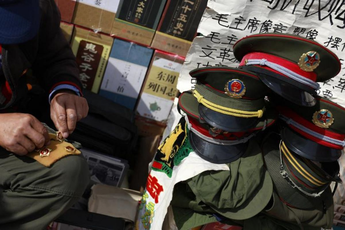 A Chinese stall owner displaying Chinese Communist Party military pins and uniforms at Panjiayuan Antique market on Oct 11.