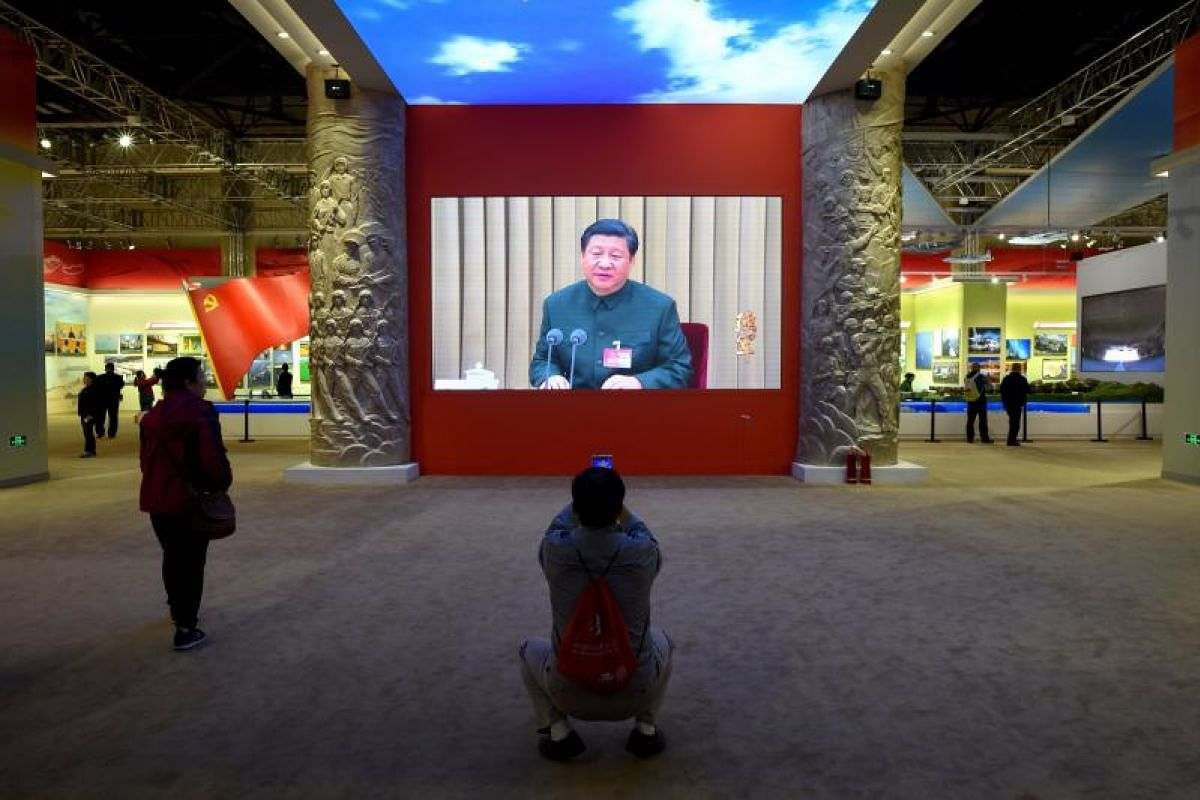 A man using a mobile phone to take a picture in front of a screen showing Chinese President Xi Jinping during an exhibition showcasing China's progress in the past five years at the Beijing Exhibition Center on Oct 10, 2017.