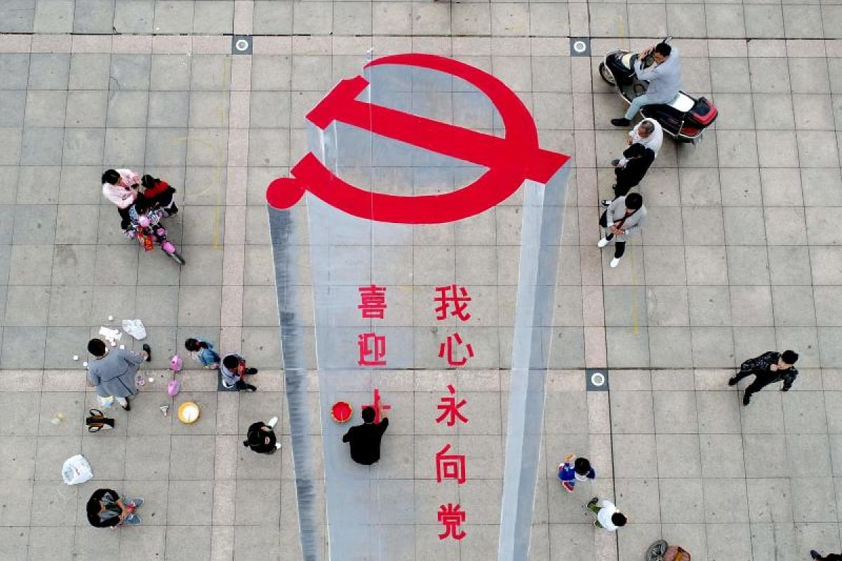 A man working on a 3D street painting of the emblem of Chinese Communist Party in Xiayi in Henan on Oct 6, 2017.