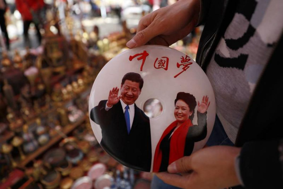 """A stall owner holding a jade plaque engraved with a picture of Chinese President Xi Jinping and his wife Peng Liyuan with the words """"China Dream"""" at Panjiayuan Antique market in Beijing on Oct 11, 2017."""
