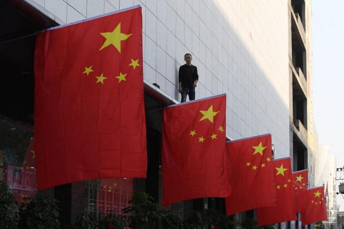 A man walking back after installing Chinese national flags outside a shopping mall in Lankao, Henan province on Sept 28, 2017.