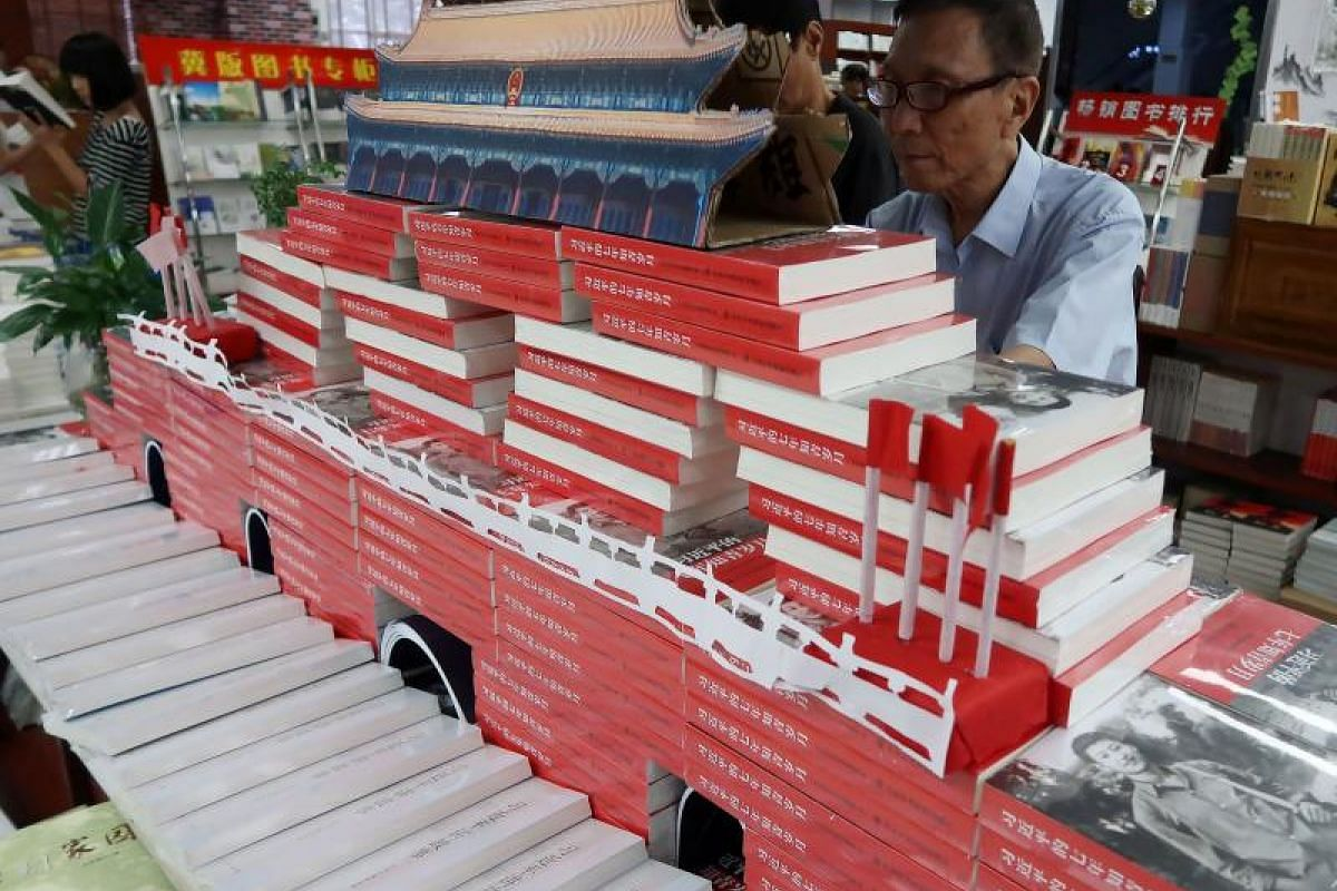 A man looking at books titled Xi Jinping's Seven Years of Educated Youth at a book store in Handan in China's northern Hebei province on Sept 24, 2017. The books have been piled up to represent the Tiananmen Rostrum.