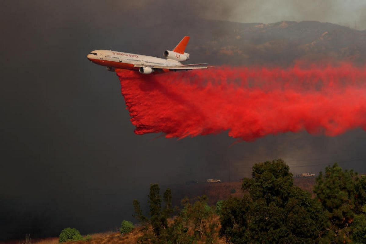 A DC-10 aircraft dropping fire retardant on a wind driven wildfire in Orange, California on Oct 9.