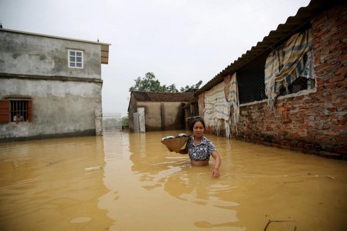 A woman standing outside her flooded house in Hoang Van Thu commune, Chuong My district in Hanoi, Vietnam on Oct 13, 2017. Heavy rain over the past few days has caused floods to many residential areas in the district. More than 200 houses have been s
