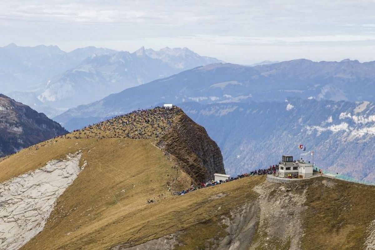 Spectators crowd on a mountaintop during a shooting event of the Swiss Air Force on Oct 12, 2017. Every autumn, the Swiss Air Force pilots show their skills in the Swiss Alps above Axalp Ebenfluh.