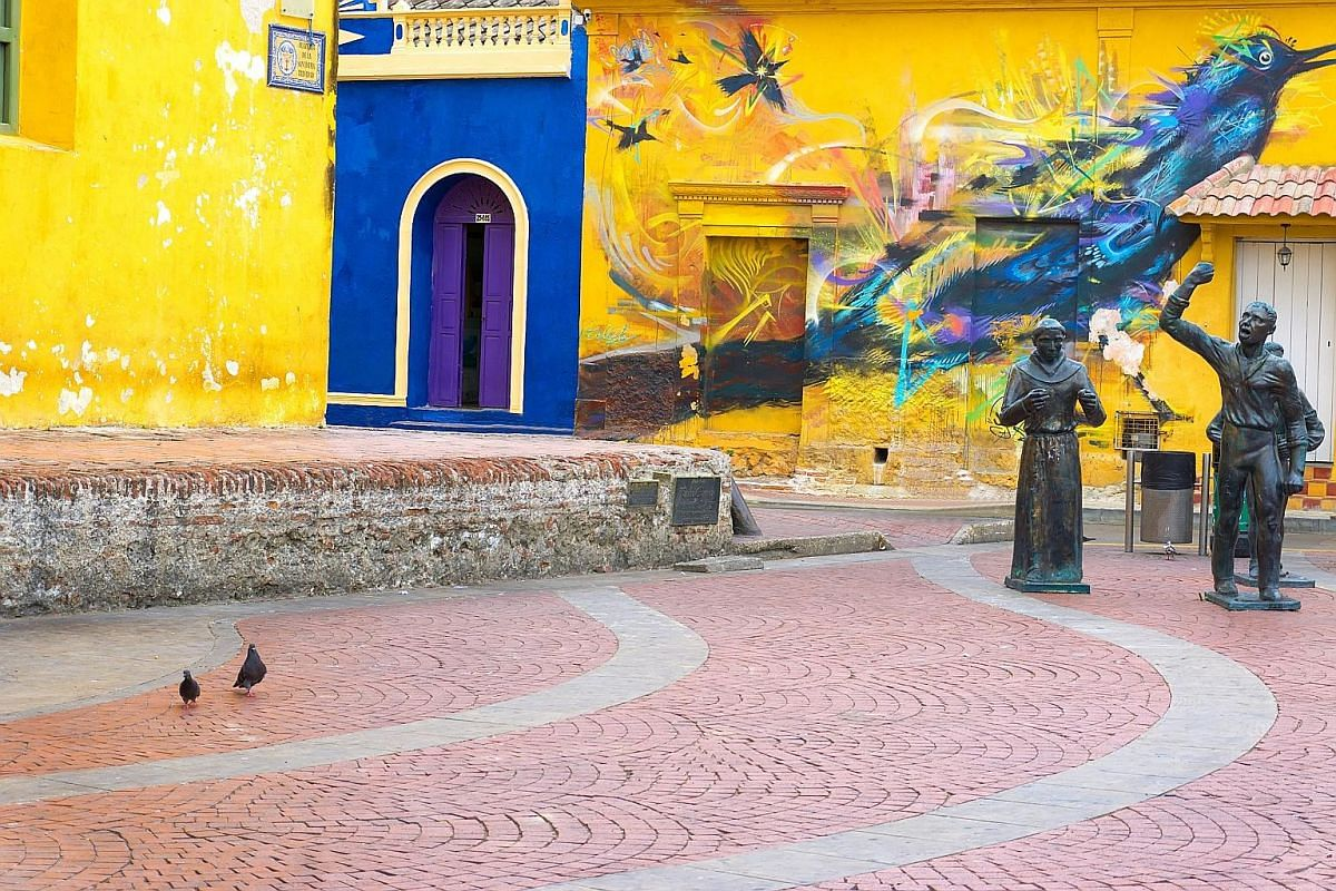Statues and a mural in Santisima Trinidad Plaza in Cartagena, Colombia.