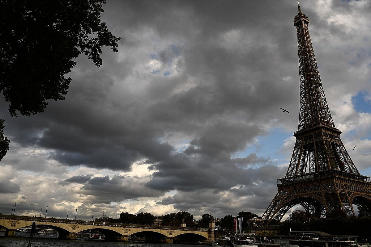 A view of the Eiffel Tower taken from the embankment of the Seine River in Paris.