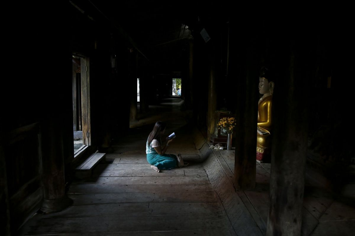 A girl worships in front of a Buddha stupa as she prays inside Bagaya monastery at Inwa,central Myanmar, 15 October 2017. Bagaya monastery (Bagaya Kyaung) was built in 1834 during the reign of King Bagyidaw. Being built entirely of teak wood, the mon