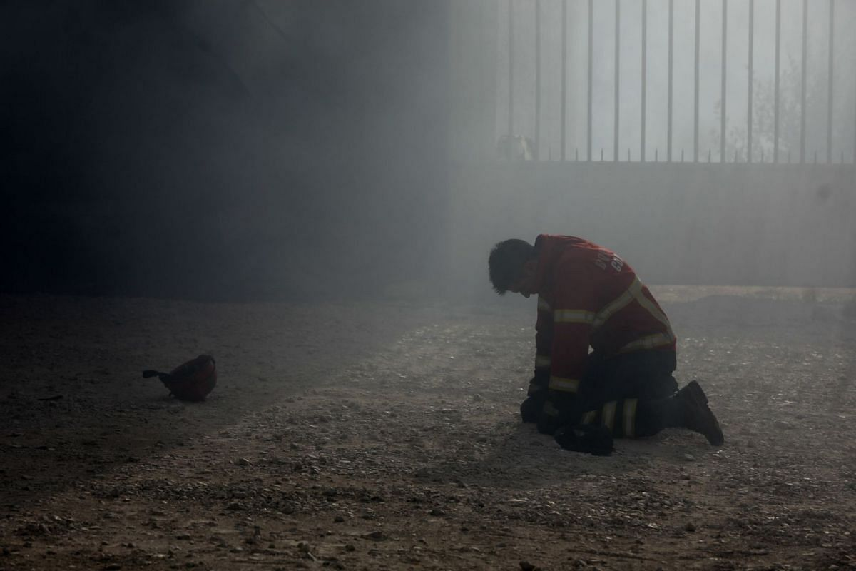 A firefighter kneels on the ground duringg a fire in Vila Nova de Poiares, Lousa, Portugal, October 15, 2017. The National Civil Protection Authority (ANPC) said it 'was the worst day of the year in terms of fires', having exceeded 300 forest fires.