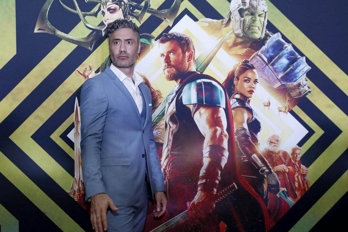 New Zealand director Taika Waititi poses before a poster of Thor: Ragnarok at the Australian premiere.
