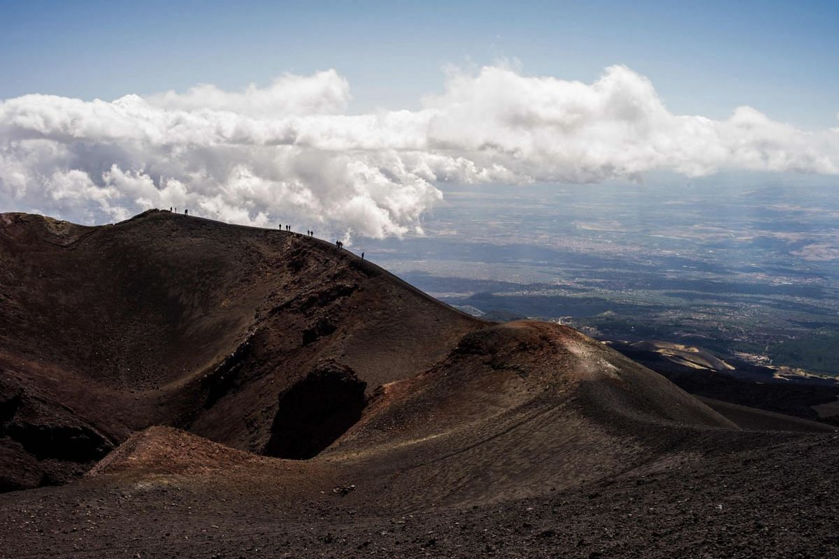 People hike on September 21, 2017 on the Mount Etna volcano on the Italian island of Sicily.