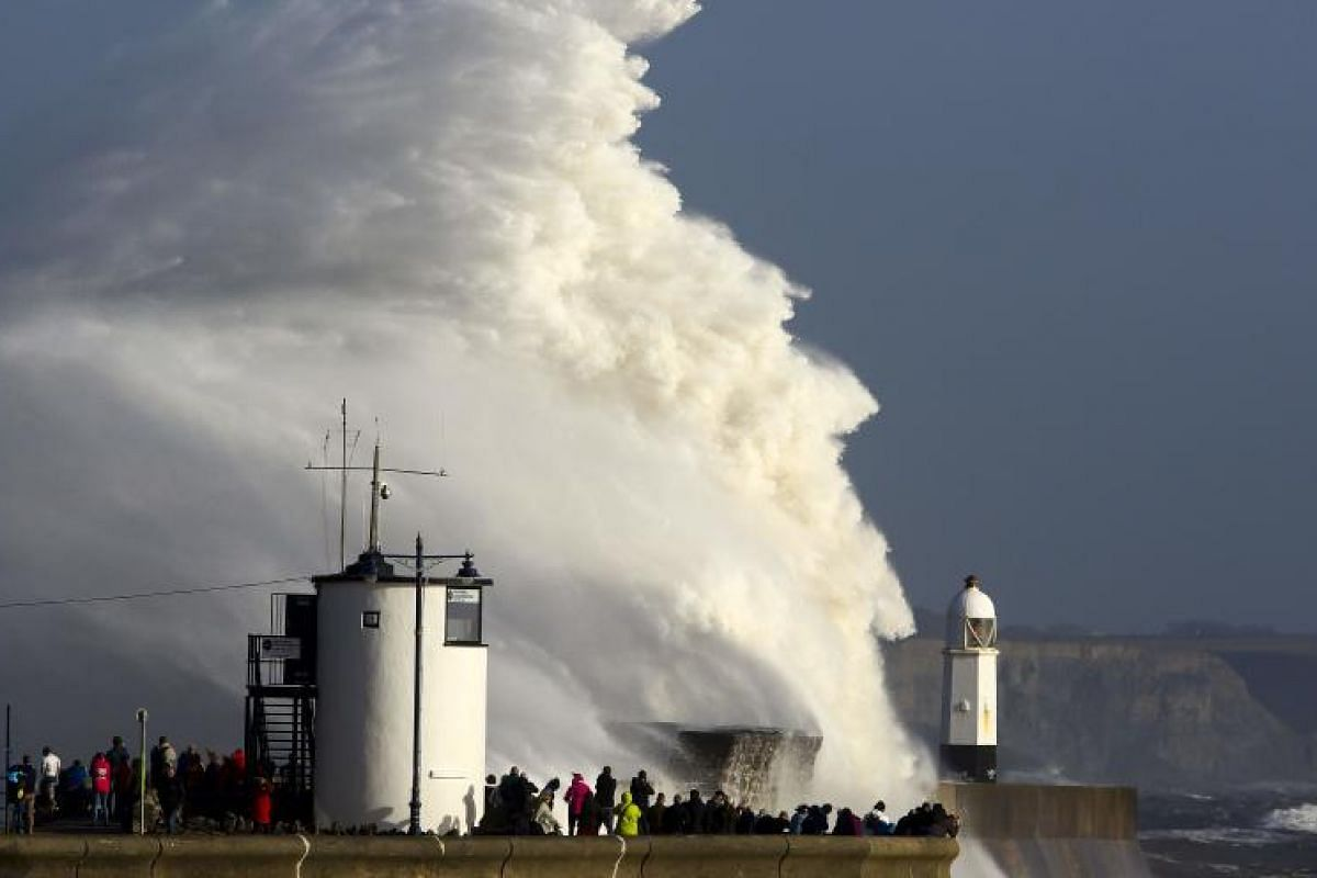 Huge waves striking the harbour wall and lighthouse at Porthcawl, south Wales, on Oct 16, 2017 as Storm Ophelia hits the UK and Ireland. The storm sent strong winds over the southwest of England and the south and west of Wales.