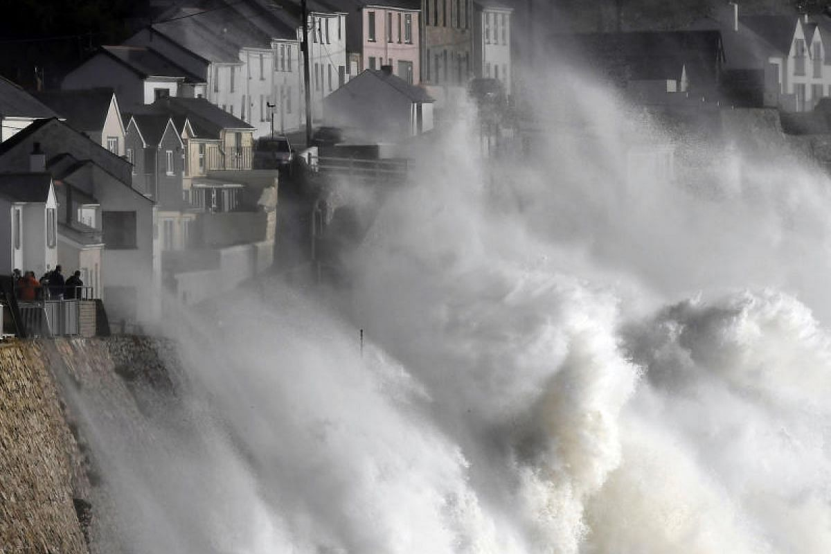 Large waves crashing along sea defences and the harbour as storm Ophelia approaches Porthleven in Cornwall, south west Britain on Oct 16, 2017.