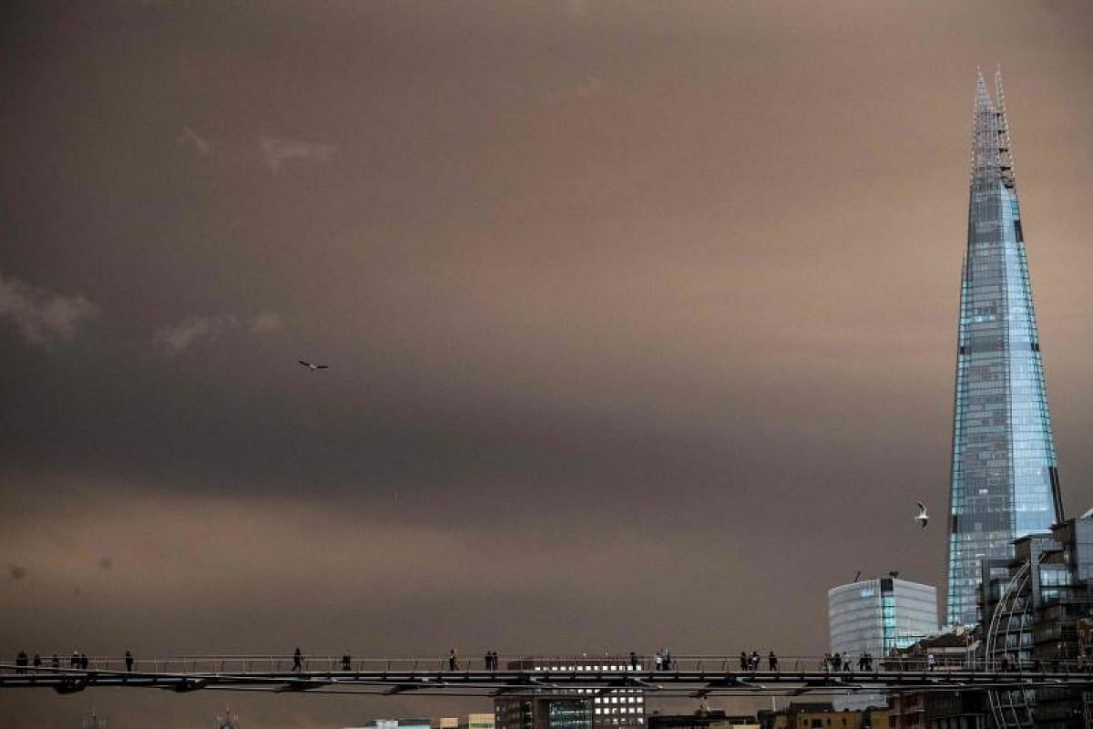 Pedestrians crossing the Millennium Footbridge with the sky darkened over London on Oct 16, 2017 due to warm air and dust swept up by storm Ophelia.