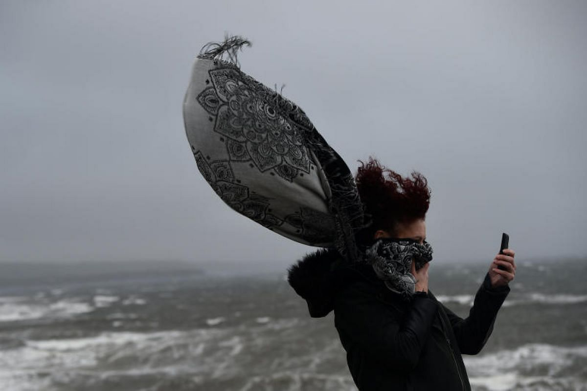 A woman taking a picture during storm Ophelia in the County Clare town of Lahinch, Ireland on Oct 16, 2017.