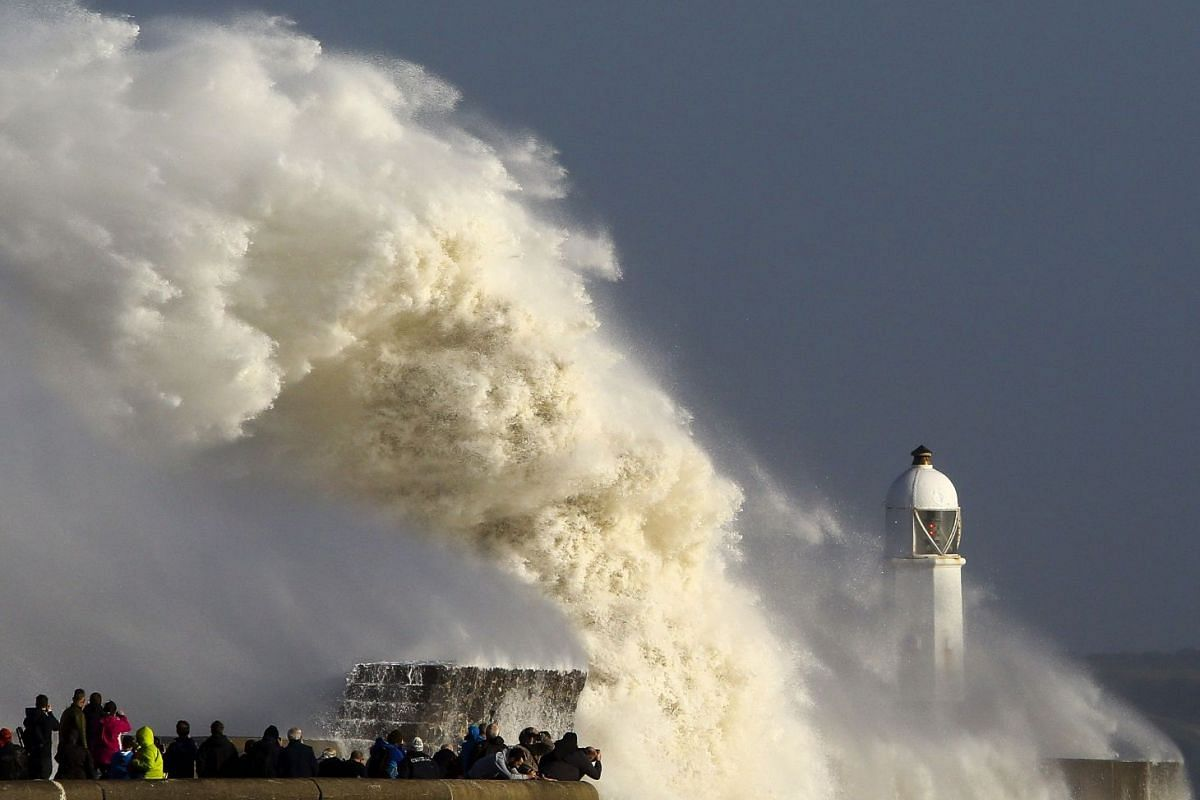 """Huge waves strike the harbour wall and lighthouse at Porthcawl, south Wales, on October 16, 2017 as Storm Ophelia hits the UK and Ireland. Ireland was hit by an """"unprecedented storm"""" on Monday that left two people dead, 120,000 homes and businesses w"""