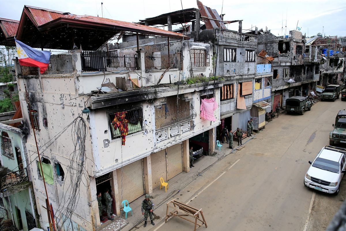 Government soldiers standing guard in front of damaged houses and buildings in Mapandi district in Marawi city, southern Philippines, on Sept 13, 2017.