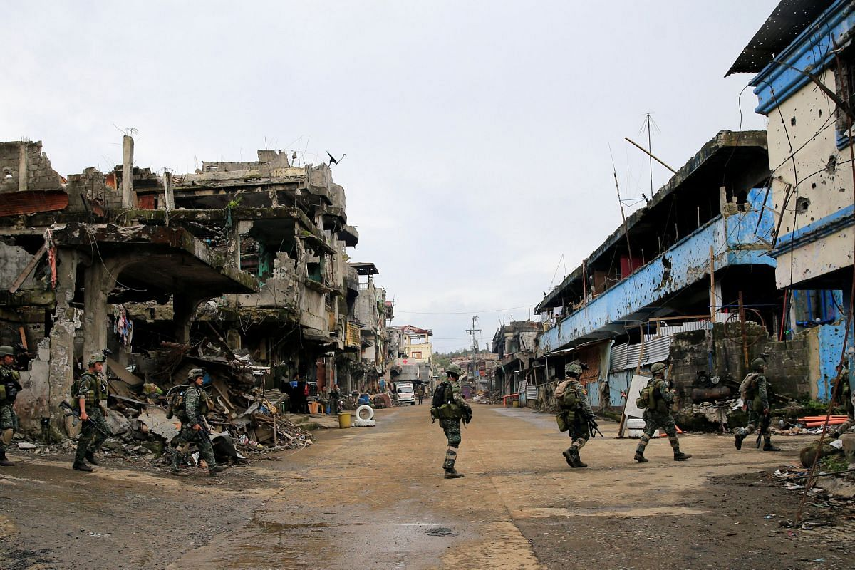 Government soldiers patrolling near damaged buildings and houses on Sept 4, 2017, as troops continue their assault on its 105th day of clearing operations against pro-ISIS militants who have seized control of large parts of Marawi City.