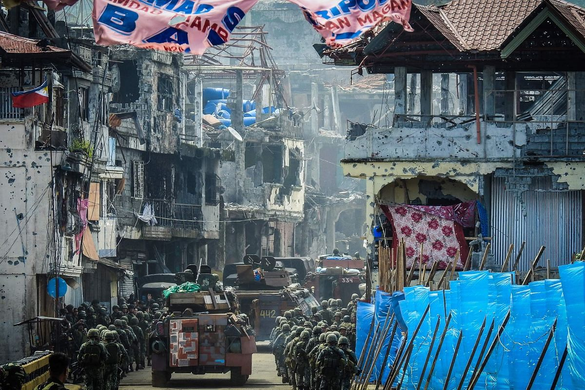 Philippine Marines, marching in formation alongside armoured personnel carriers, head to the frontline past damaged buildings in the Mapandi area of Marawi on Aug 30, 2017, as fighting between government troops and pro-ISIS militants entered its 100t
