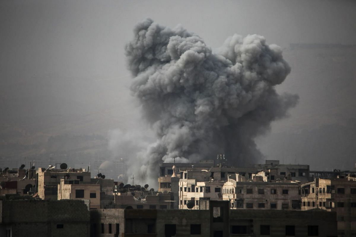 Smoke billows from buildings following a reported air strike on Ain Tarma in the Eastern Ghouta area, a rebel stronghold east of the Syrian capital, on October 16, 2017.