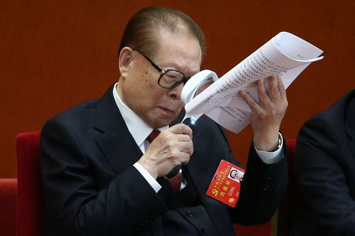 Former Chinese President Jiang Zemin holding a magnifying glass while reading a document during the opening ceremony of the 19th National Congress of the Communist Party of China at the Great Hall of the People in Beijing on Oct 18, 2017.