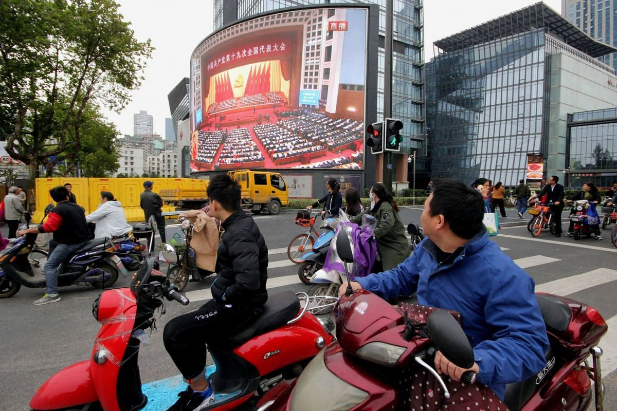 People watching a broadcast of Chinese President Xi Jinping delivering his speech during the opening of the 19th National Congress of the Communist Party of China, on a giant outdoor screen in Nanjing, Jiangsu province, China on Oct 18, 2017.