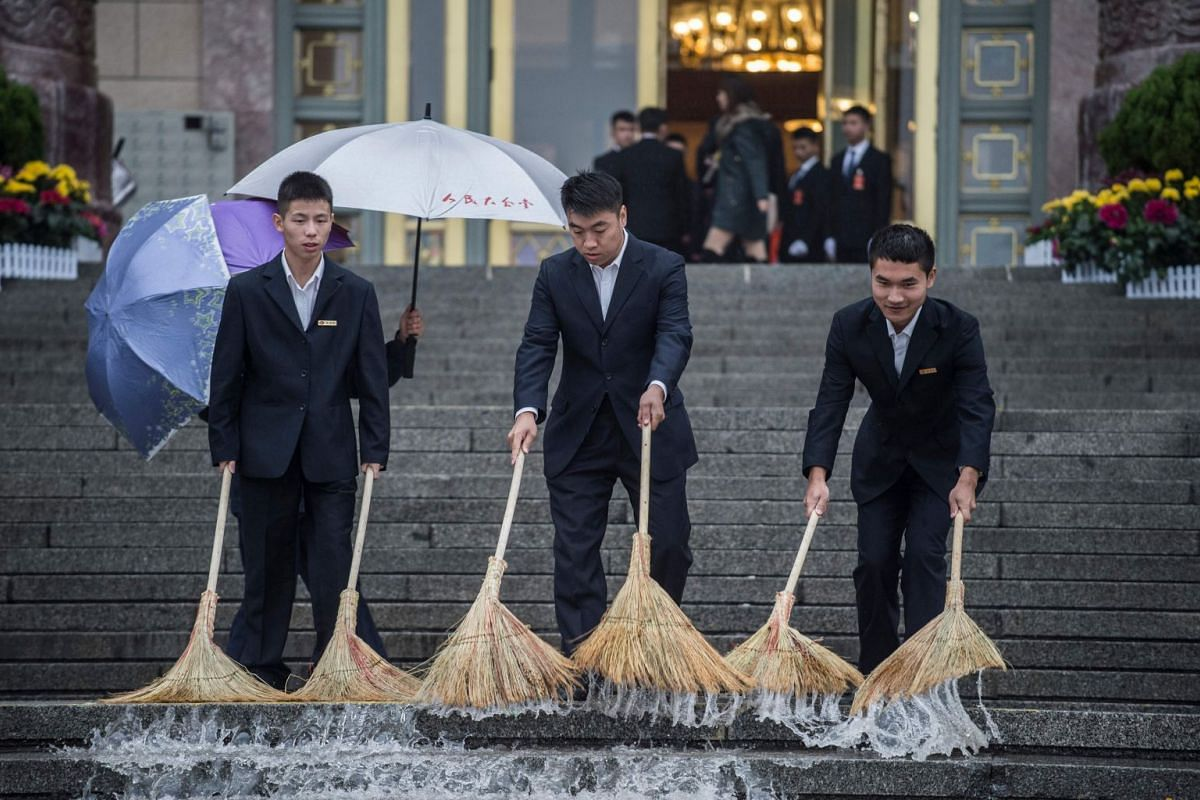 Chinese security guards sweeping water at the start of the Communist Party's 19th Congress in Beijing on Oct 18, 2017.