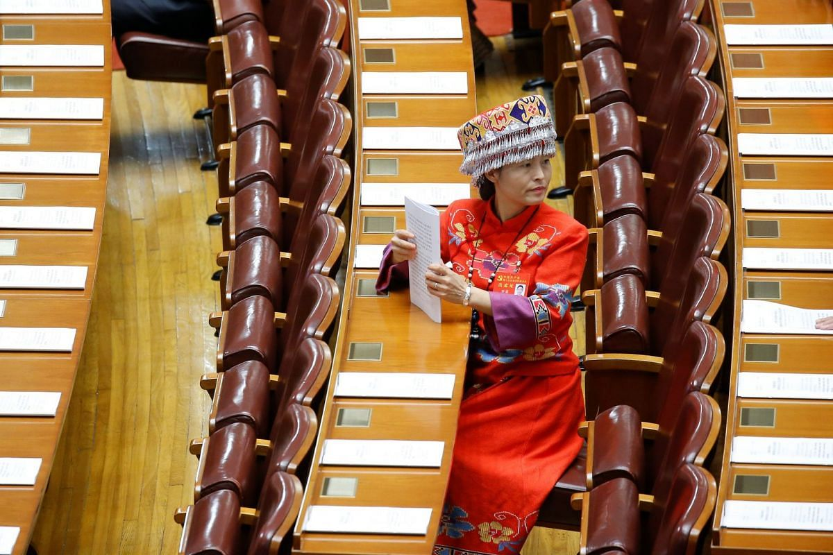A delegate wearing traditional costume preparing for the opening session of the 19th National Congress of the Communist Party of China at the Great Hall of the People in Beijing on Oct 18, 2017.