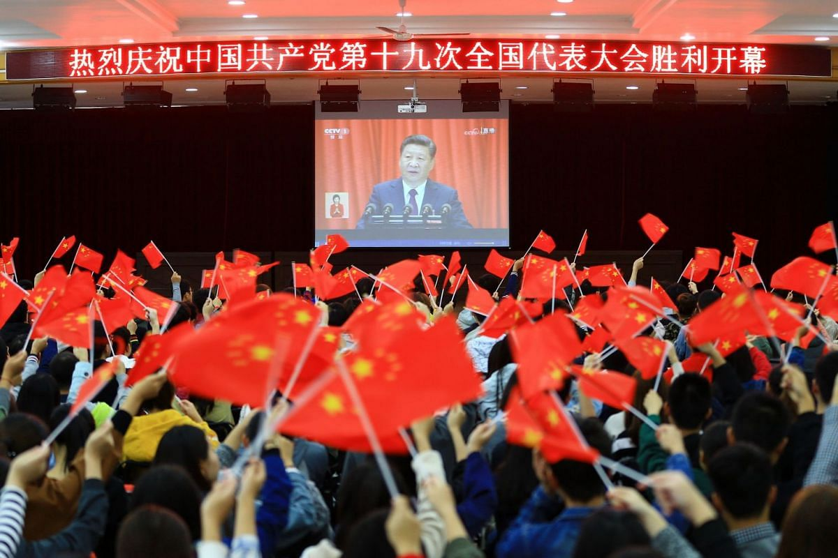 Chinese college students waving national flags as they watch the opening of the 19th Communist Party Congress in Huaibei in the country's eastern Anhui province on Oct 18, 2017.