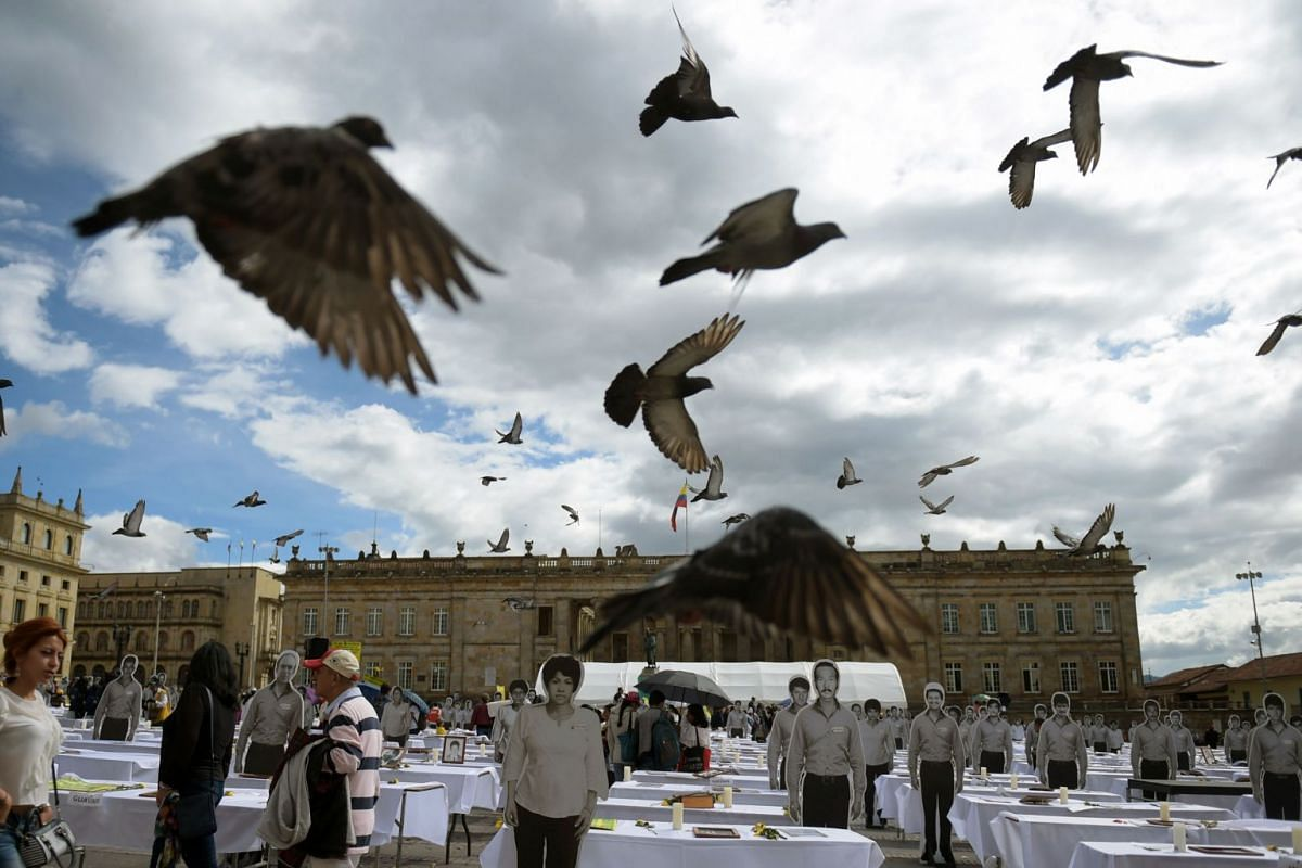 Doves fly over life-size images of killed and missing members of the Patriotic Union (UP), displayed during a tribute to the victims of Colombia's armed conflict at Bolivar Square in Bogota on Oct 19, 2017.