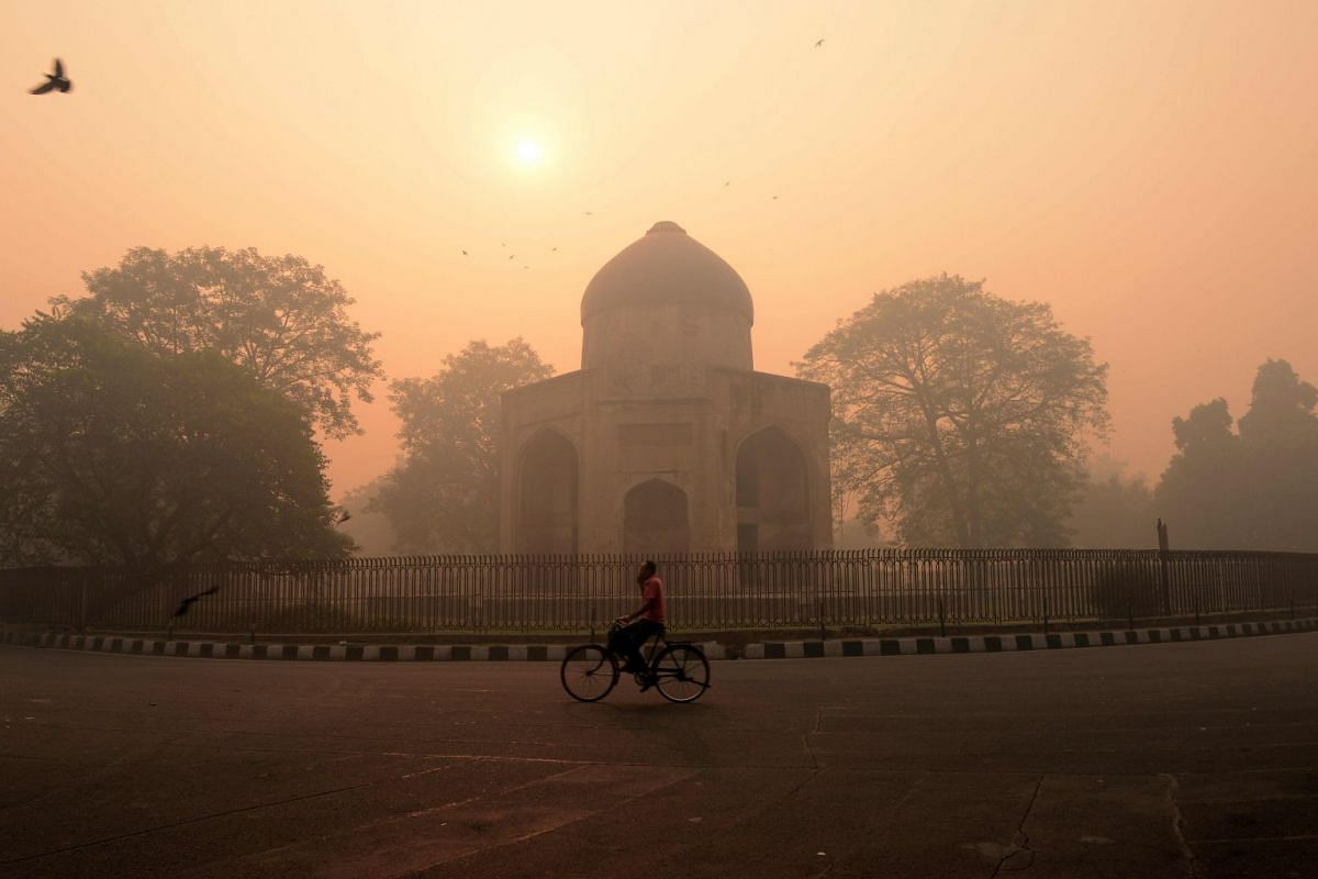 This file photo taken last year shows an Indian cyclist riding along a street as smog envelops a monument in New Delhi. Pollution had claimed the lives of nine million people in 2015, one in every six deaths that year, according to a report published