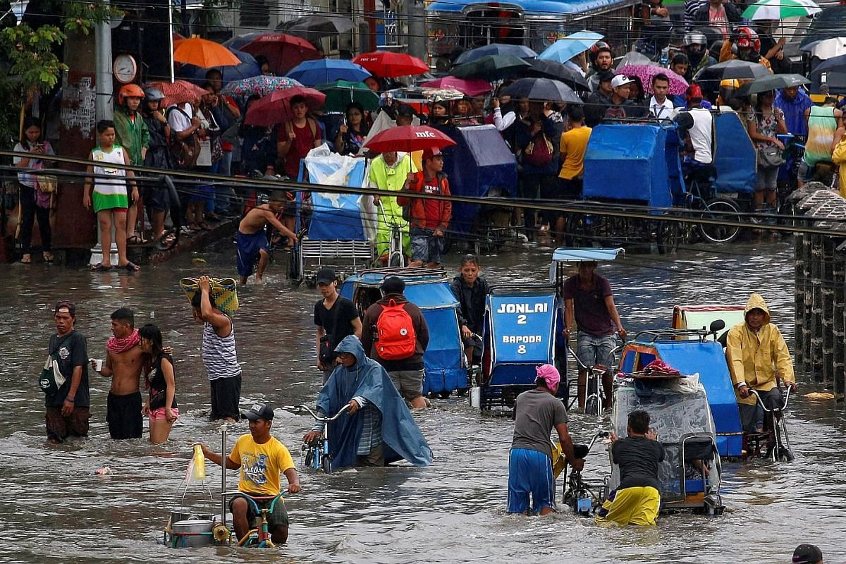 Above: Residents awaiting their turn to make their way by pedicab through floodwaters in Metro Manila last month. Left: Tacloban in the days after being hit by Super Typhoon Haiyan in 2013. Almost nothing was left standing in the trading hub of 200,0
