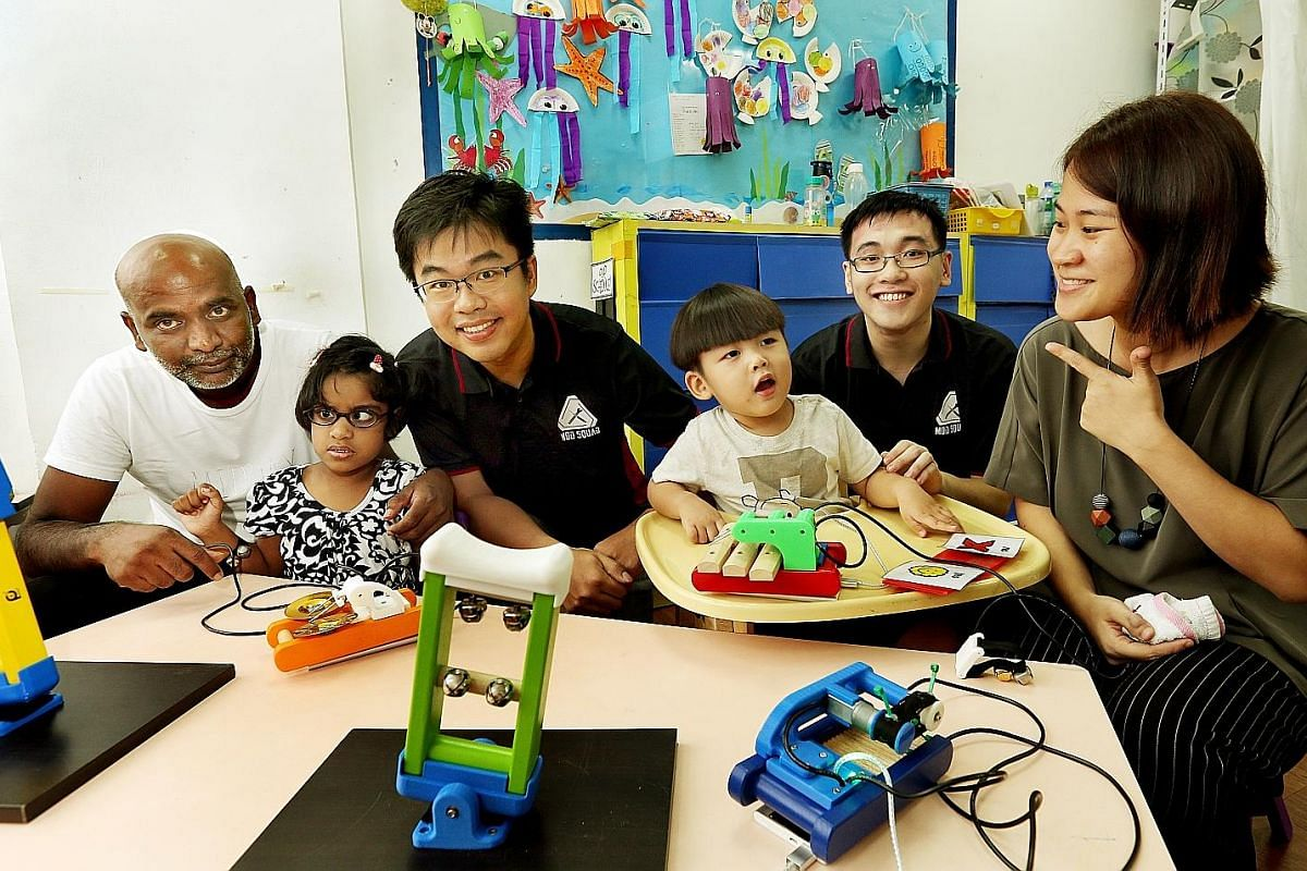 Mr Jain Rathan with his daughter Mackenzia Gabriella and Mrs Teo Wei Lin with her son Reon. The children are playing with the modified musical instruments created by engineers from DSO National Laboratories, Mr Yee Qing Xiang (third from left) and Mr
