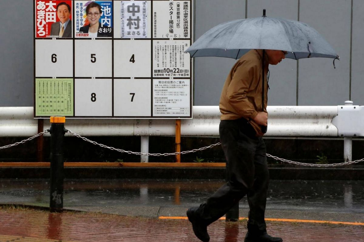 A man walks in the rain past election posters near a polling station as Typhoon Lan approaches Japan's mainland, in Tokyo, Japan, on Oct 22, 2017.