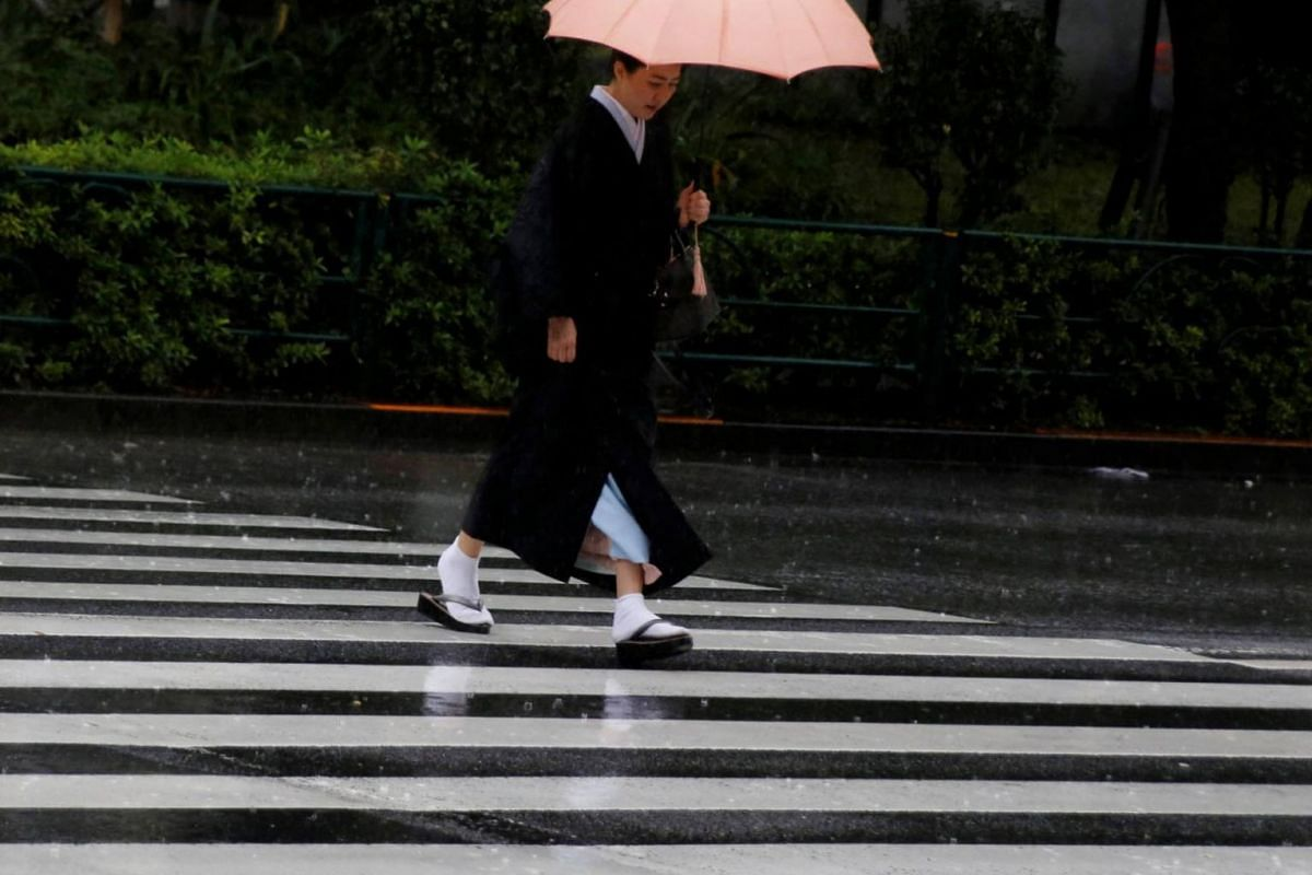 A woman in a kimono crosses a road in heavy rain as Typhoon Lan approaches Japan's mainland, in Tokyo, Japan, on Oct 22, 2017.