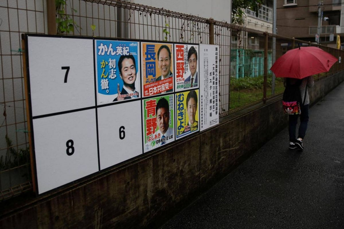 A woman walks in the rain past election posters as Typhoon Lan approaches Japan's mainland, in Osaka, western Japan, on Oct 22, 2017.