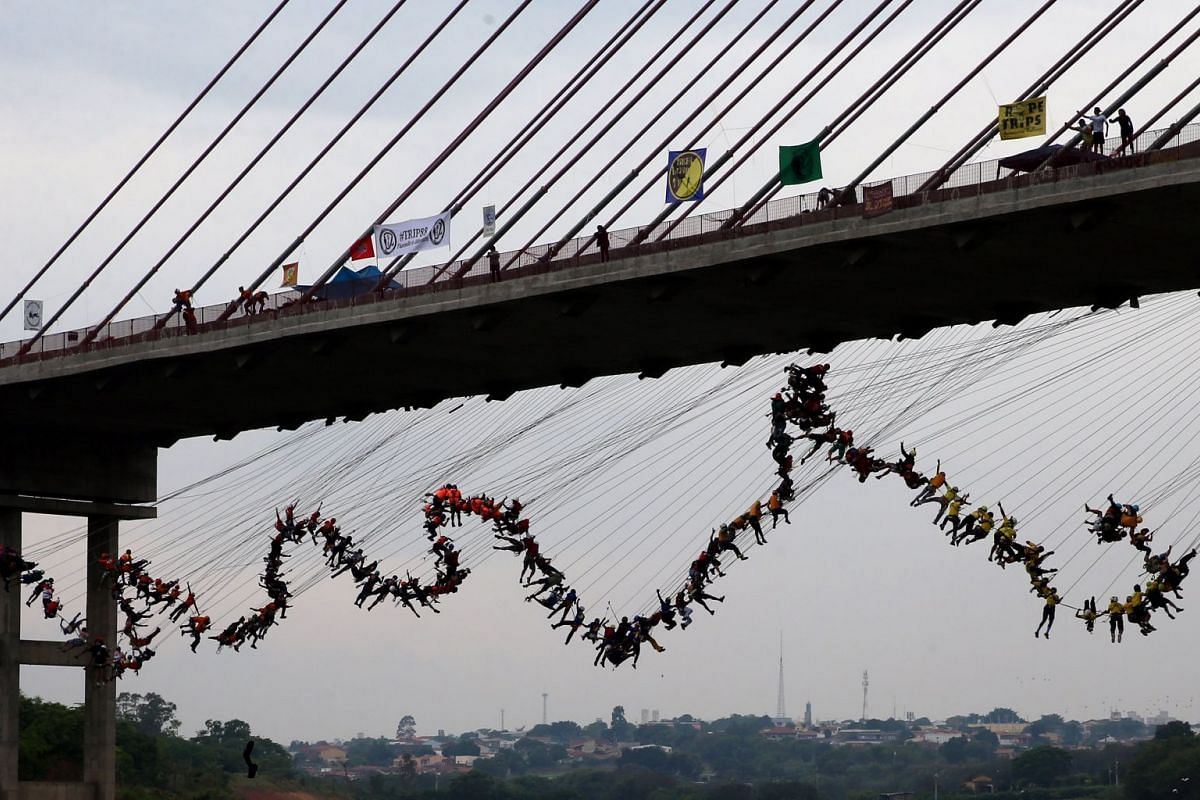 """People jump off a bridge, which has a height of 30 meters, in Hortolandia, Brazil, October 22, 2017. According to organizers, 245 people were attempting set a new world record for """"rope jumping"""", in which people, tied to a safety cord, jump off a bri"""