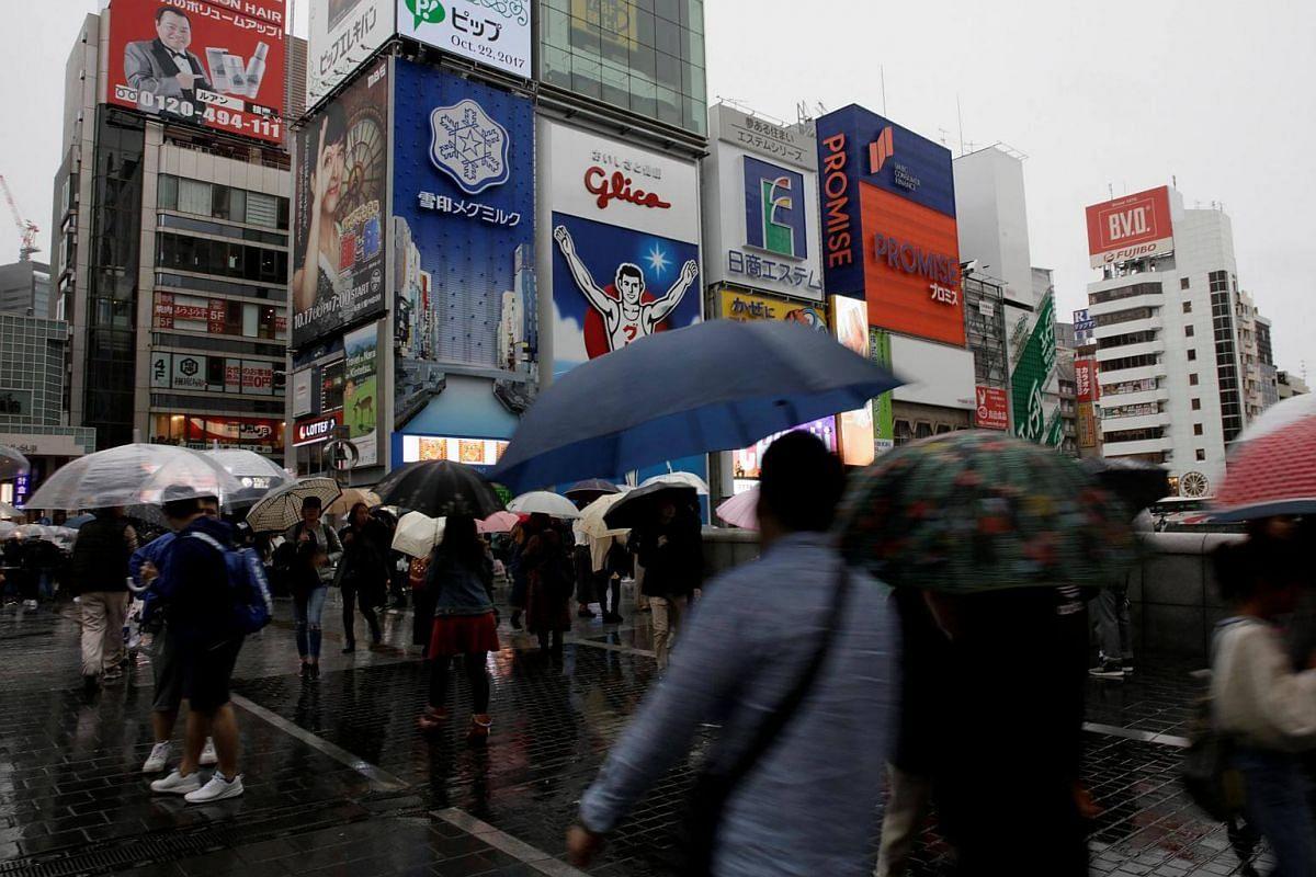 Shoppers walk under umbrellas as Typhoon Lan approaches Japan's mainland, in Osaka, on Oct 22, 2017.
