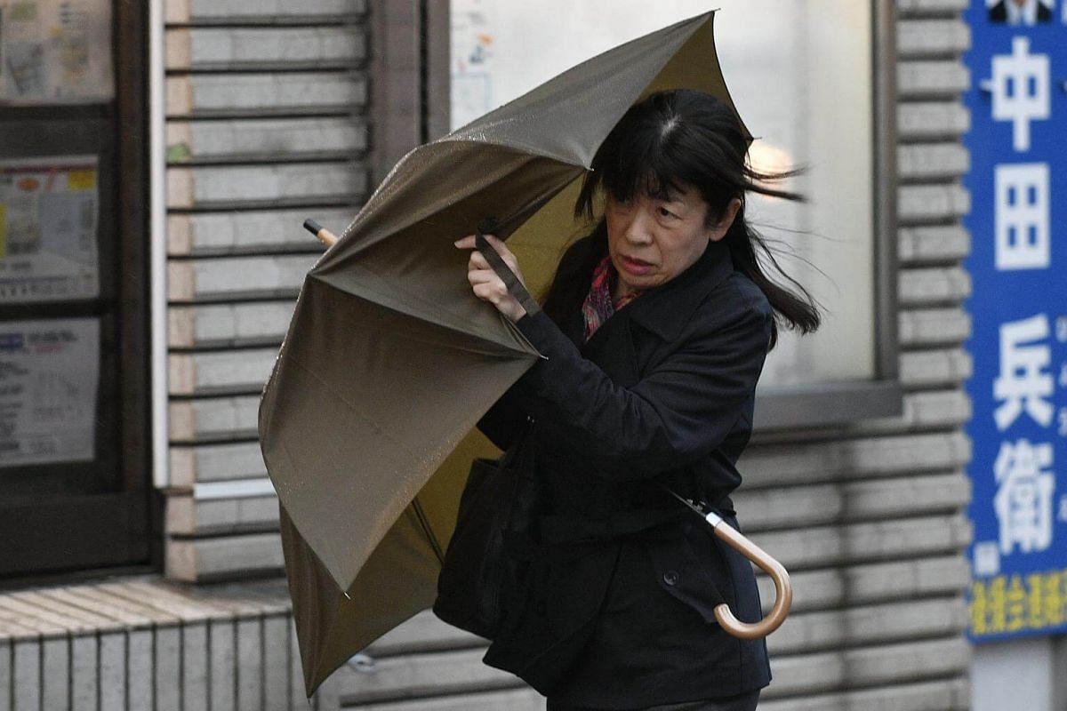 A woman shields herself from strong wind generated by typhoon Lan in Tokyo, on Oct 23, 2017.