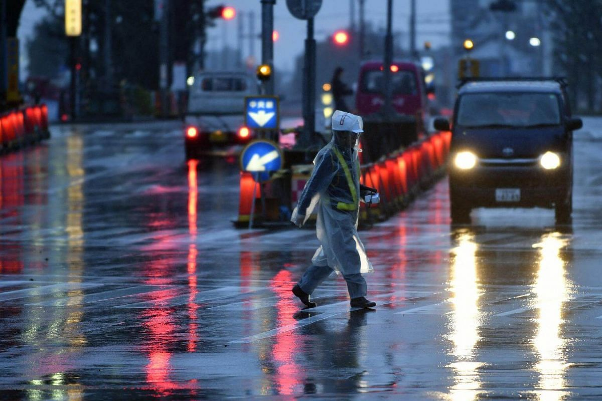 A man crosses a street under strong wind and rain generated by typhoon Lan in Tokyo, on Oct 23, 2017.