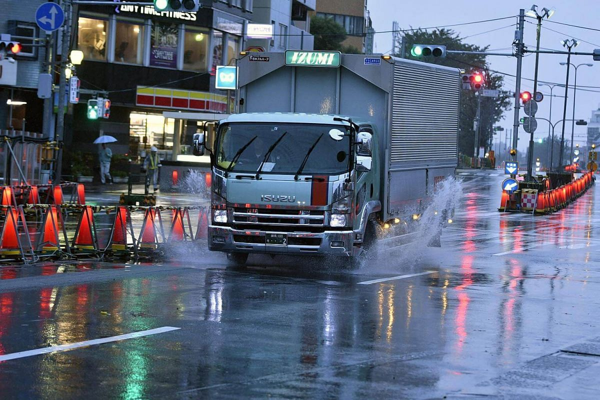 A truck splashes water under strong rain and wind generated by typhoon Lan in Tokyo, on Oct 23, 2017.