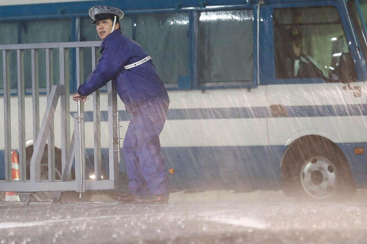 A policeman stands guard in the heavy rain outside the headquarters of Japan's ruling Liberal Democratic Party (LDP) in Tokyo, on Oct 22, 2017.
