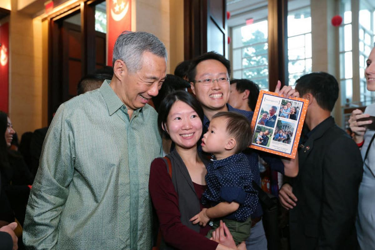 PM Lee takes a photo with Mr Eric Cheung, 33, his wife Crystal Lim, 30, and their son Dayton Cheung, 2, at a reception with Singaporeans at the Singapore Embassy in Washington on Sunday (Oct 22).