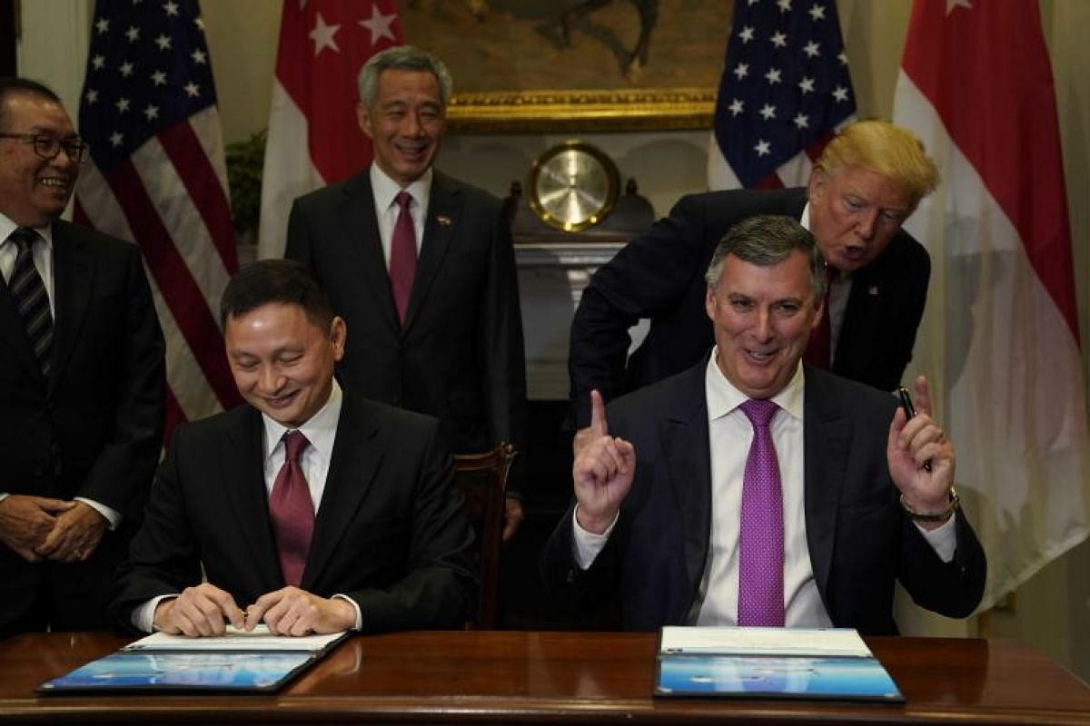 Singapore Airlines CEO Goh Choon Phong (left) and Boeing's commercial airplanes CEO Kevin McAllister sign a sales contract for planes in the Roosevelt Room, witnessed by PM Lee and President Trump on Monday (Oct 23).
