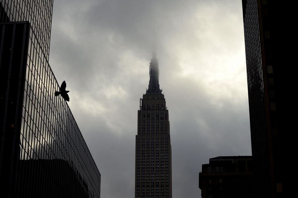 The Empire State Buiding is surrounded in the morning fog as the sun comes in New York October 23, 2017.