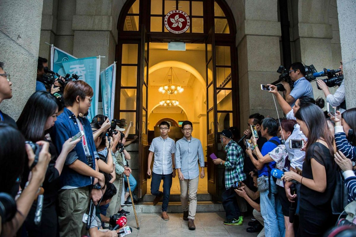 Pro-democracy activists and Demosisto members Joshua Wong (centre, left) and Nathan Law (centre, right) walk from the Court of Final Appeal after their bail applications were successful at Hong Kong's highest court, on Oct 24, 2017. PHOTO: AFP