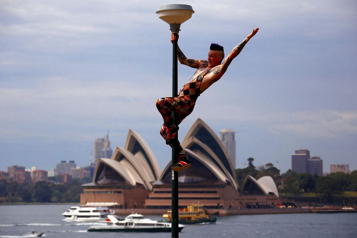 Performer Mitch Jones from Circus Oz reacts after climbing a light pole during the official launch of the annual cultural celebration The Sydney Festival, which showcases theatre, dance, circus, visual art and music during the month of January, in a