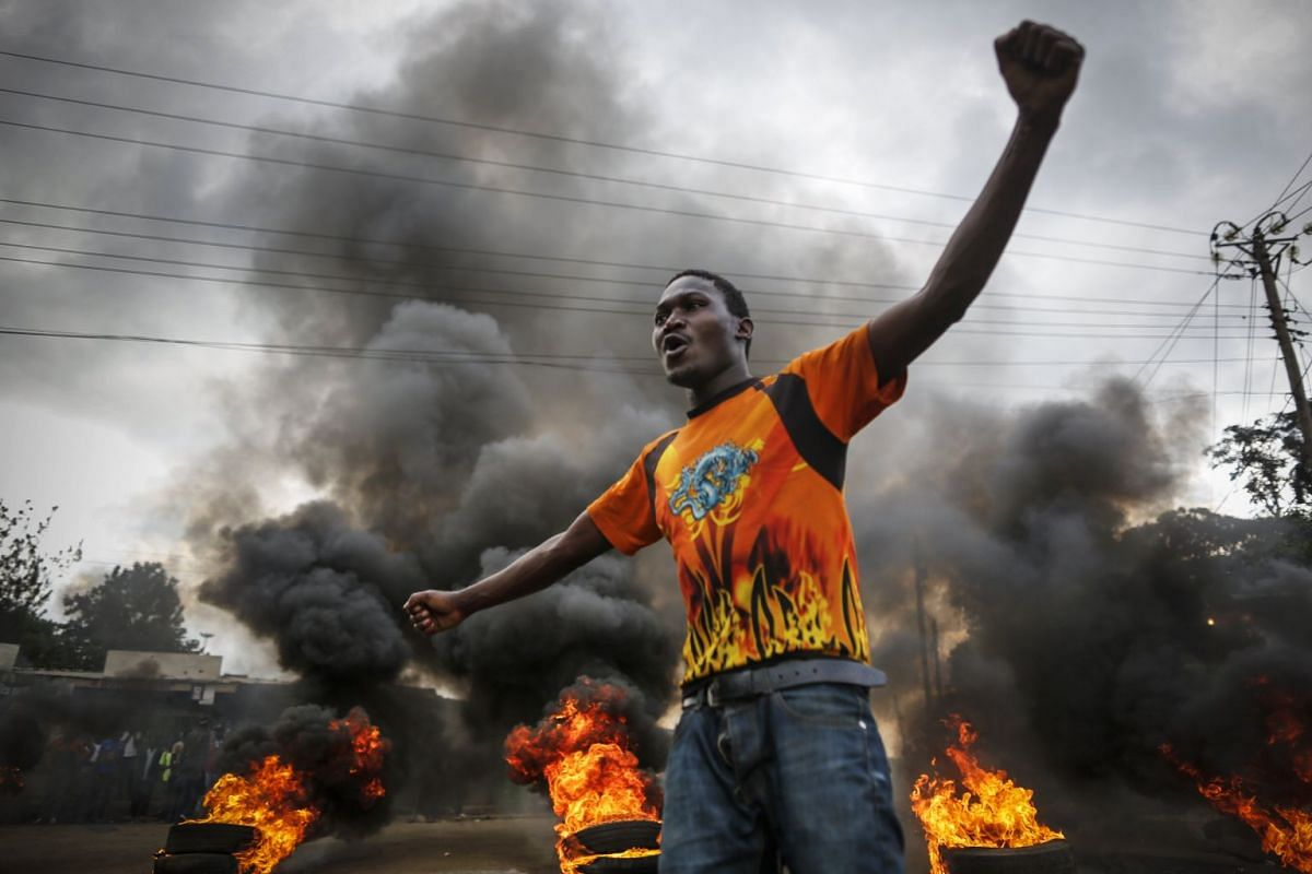 A supporter of the opposition coalition the National Super Alliance (NASA) and its presidential candidate Raila Odinga reacts in front of a burning barricade he and others set up to block vehicles from delivering electoral materials to the polling st